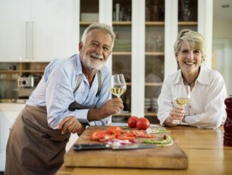 Two senior people standing -dinner-table