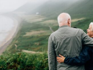 A couple standing on the mountain in front of the sea.