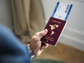 A person holding a passport and ticket.