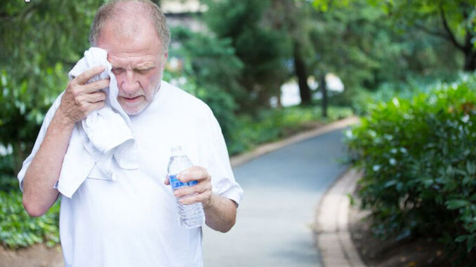 A senior man cleaning sweat and drinking water when walking on the park.