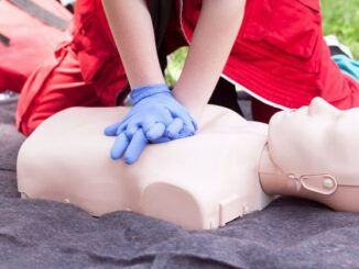 A person do CPR on a dummy.