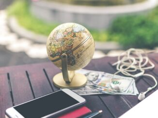 HealthyLivingLinks-globe on a table and phone, earphone, US dollars and a pen