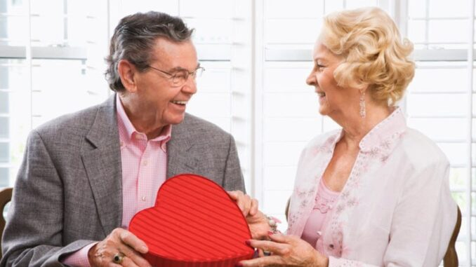 A happy senior couple- a husband give a gift to his wife
