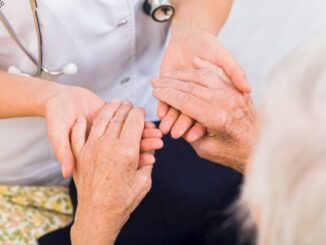 A nurse holding a senior patient hands