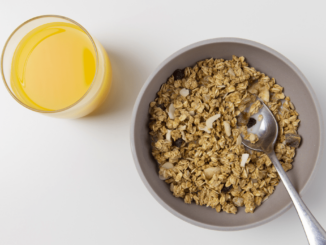 A bowl of cereals and a glass of juice
