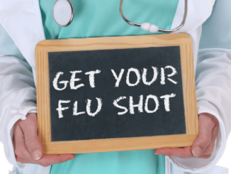 """A doctor holding a board with """"get your flu shot"""""""