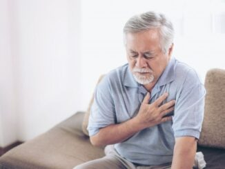 A senior man holding his heart bc of heart attack