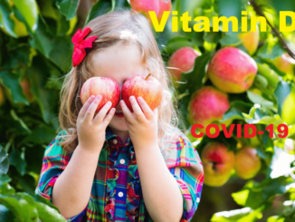 A young girl standing in front of the apple tree with two apples cover her eyes with phase vitamin D and covid 19