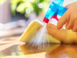 A person wearing yellow gloves spraying cleaning liquid on the table