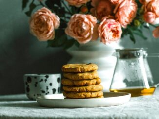 A table with a dish of cookies, tea and bottle of flowers