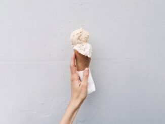 A person holding an ice cream in cone