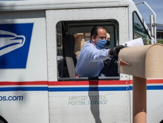The shipping man putting a letter to mail box.