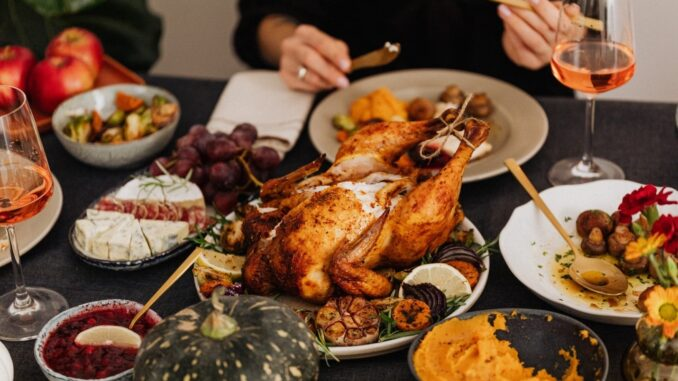 A table have many kind of food and big roast turkey.