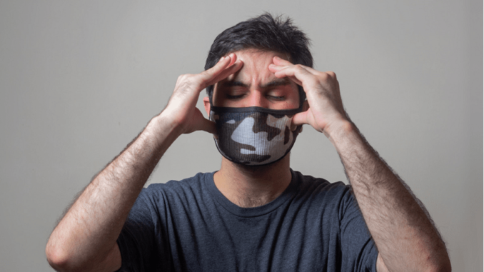 Imitrex- A man wearing a mask and holding his head